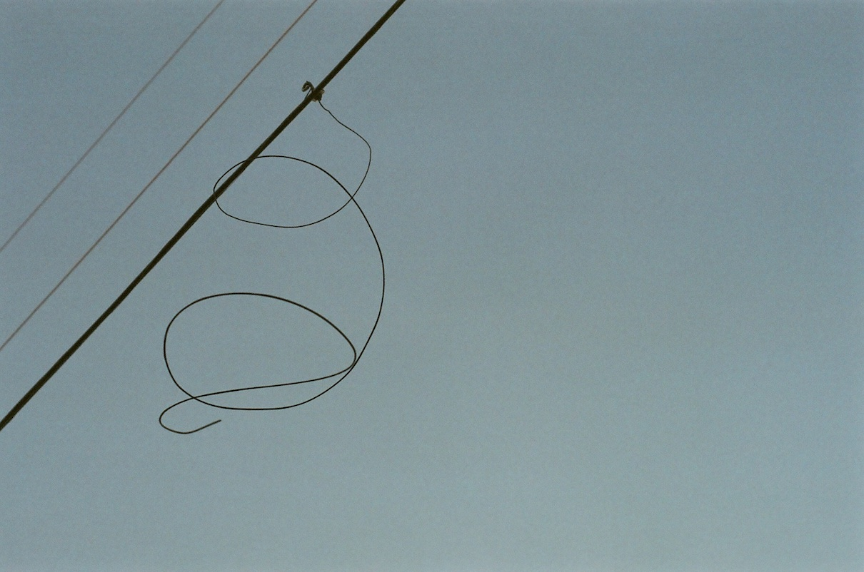 I like the shape of this wire hanging from the power line near my house -- it looks like a little scribble-dude hanging on for dear life..