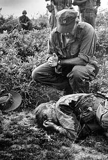 U.S. Marine Corps chaplain John Monamara of Boston administers the last rites to war correspondent Dickey Chapelle.  HENRI HUET, Chu Lai, Vietnam, 1965 -- AP