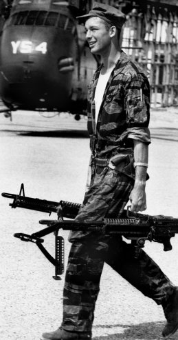 Yankee Papa 13 crew chief James Farley carries M-60 machine guns to the helicopter.  LARRY BURROWS, Near Da Nang, Vietnam, 1965  -- Larry Burrows—Time & Life Pictures/Getty Images