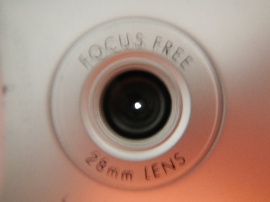 It's actually a tiny pinhole and nice and round -- I checked with a 32X loupe.  Holdng it up to the light with the back open while I took a macro shot with another camera made things a bit blurry.