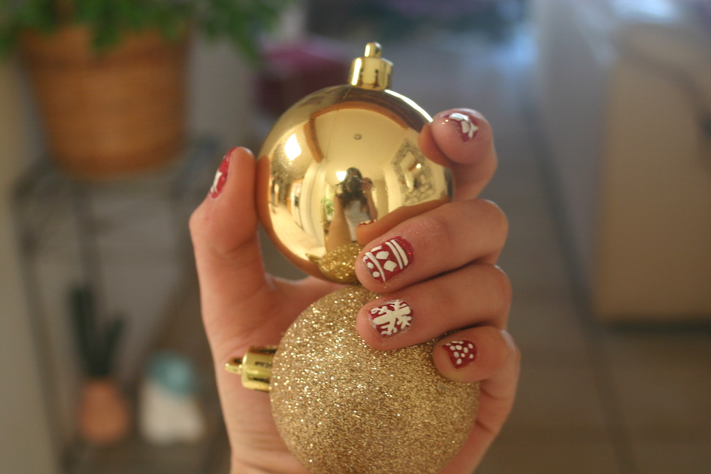 Christmas ornament selfie with festive nails.