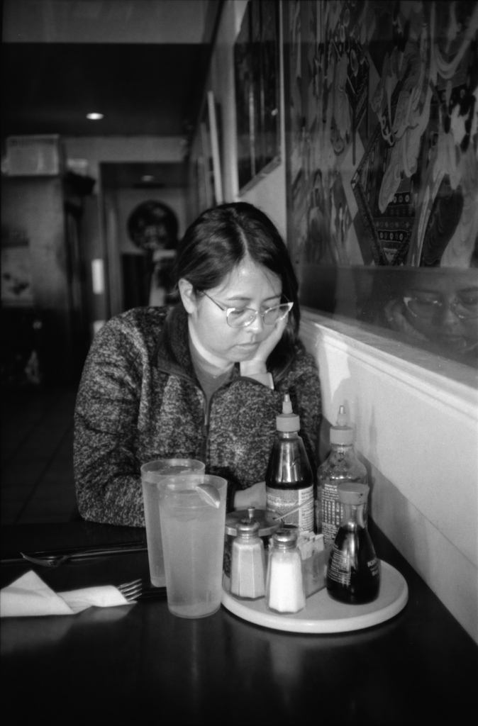 M ponders an article on her phone at Pho Kim.