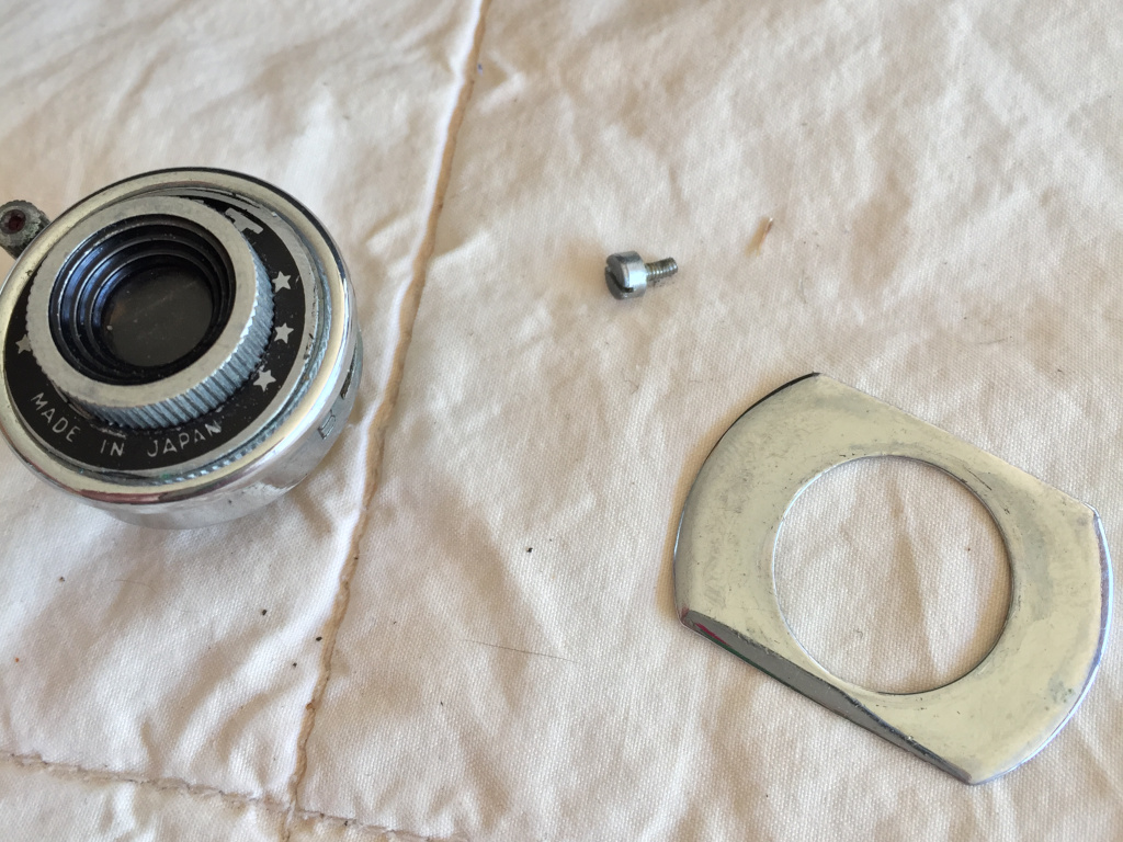 The lens/shutter assembly comes out after removing the ring. The little screw is the Instant/Bulb selector. It didn't need to come off but I didn't know that at the time. The trim plate acts as a washer so it might be part of the lens distance as well as being cosmetic.